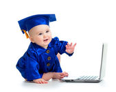Happy child in academician clothes  using laptop — Stock Photo