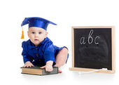Baby in academician clothes  with book at chalkboard — Stock Photo
