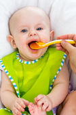 Baby feeding with a spoon — Stock Photo