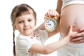 Kid with an alarm clock and pregnant woman belly  — Stock Photo