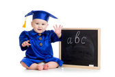 Baby in academician clothes  sitting at chalkboard — Stock Photo