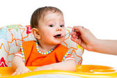 Little baby feeding with a spoon — Stock Photo