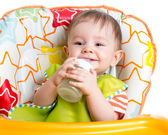Smiling baby drinking from bottle sitting in high chair — Stock Photo