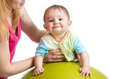 Mom doing gymnastics to her son baby on fitness ball — Stock Photo