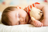 Infant baby sleeping with plush toy — Stock Photo