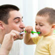 Child boy and his dad brushing teeth in bathroom — Stock Photo #45018929