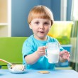Baby boy drinking milk indoors — Stock Photo