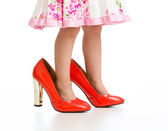 Little girl in big mommy shoes isolated on white  — Stock Photo