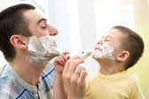 Playful father and his son shaving and having fun in bathroom — Stock Photo