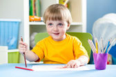 Kid boy drawing with pencils indoors — Stock Photo