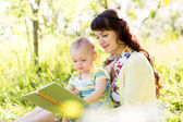 Happy mother reading a book to child outdoors — Stock Photo