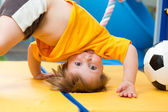 Baby standing upside down on gym mat — Stock Photo