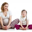 Young pregnant woman with little kid doing yoga exercises — Stock Photo