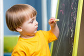 Little boy draws with chalk on blackboard — Stock Photo