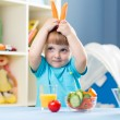 Funny kid boy eating vegetables at home interior — Stock Photo