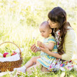 Baby and mom sit with basket outdoors — Stock Photo