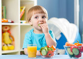 Kid boy eating vegetables at home interior — Stockfoto
