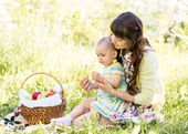 Baby and mom sit with basket outdoors — Foto de Stock