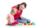 Child girl and her mom play with building blocks — Stock Photo