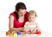 Mother and kid girl paint together at home — Stock Photo