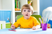 Child boy drawing with pencils at table — Foto Stock