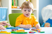 Child playing with puzzle toy indoor — Stock Photo