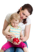 Mother and kid putting coins into piggy bank — Stock Photo
