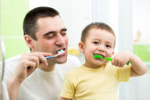 Father and kid son brushing teeth in bathroom — Stok fotoğraf