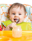 Smiling baby eating food with spoon — Stock Photo