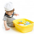 Cute baby boy with sailor hat  playing with paper boats — Stock Photo #47531131