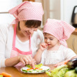 Mother and kid girl making funny face from vegetables on plate — Stock Photo #47627873