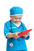 Kid boy uniformed as doctor with tablet pc in hands — Stock Photo