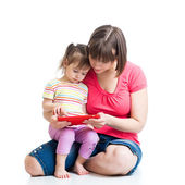 Mother and kid are looking to play and read tablet computer — Stock Photo
