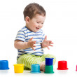 Funny baby playing with colourful cup toys on floor, isolated ov — Stock Photo #47735087