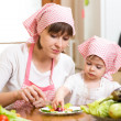 Mother and kid girl making funny face from vegetables on plate — Stock Photo