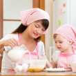 Mother and child preparing cookies together at kitchen — Stock fotografie