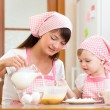 Mother and child preparing cookies together at kitchen — Foto Stock