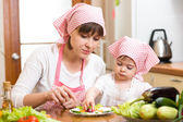 Mother and kid girl making funny face from vegetables on plate — Foto Stock