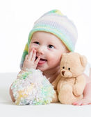 Funny baby boy lying on bed with plush toy — Stock Photo