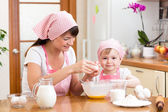 Young woman and her daughter cooking together at home — Stock Photo