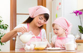 Mother and child preparing cookies together at kitchen — Stock Photo