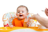 Baby sitting in highchair and eating with a spoon — Stock Photo