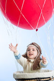 Little girl playing on hot air balloon in the sky — Stock Photo
