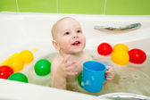 Happy kid boy taking bath and playing with toys — Stock Photo