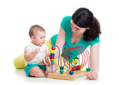 Baby girl and mother play with educational toy — Stock Photo