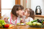 Funnt mother and kid eating vegetables in kitchen — Stock Photo