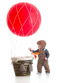 Baby with pilot hat on hot air balloon — Stock Photo