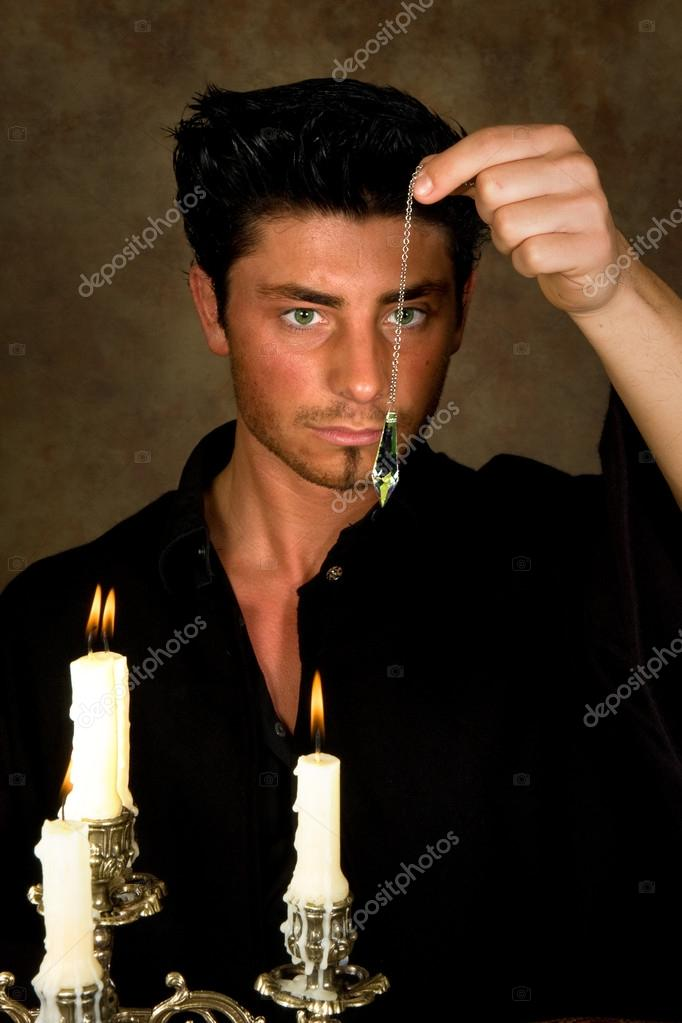 Gypsy holding his eyes on a crystal pendulum — Stock Photo #12494839