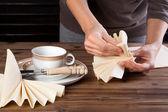 Lunch table napkin folding — Stock Photo