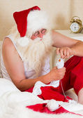 Santa Claus mending his socks — Stock Photo